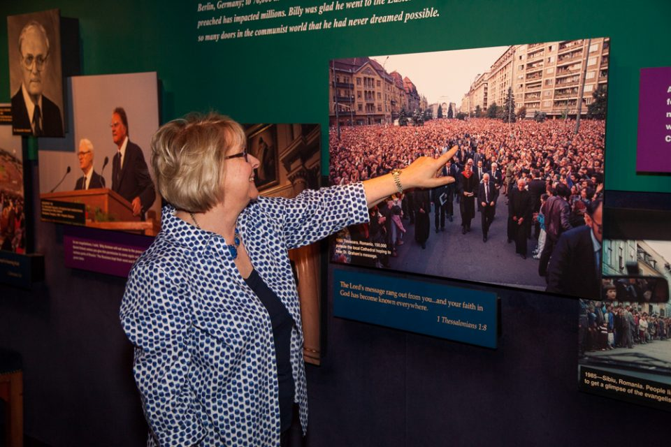Stephanie Wills identifies herself in a 1985 photo from Timisoara, Romania. She was a few paces behind Billy Graham as a massive crowd closed in. The photo can be seen at The Billy Graham Library, which is open six days a week for free tours and tells the story of how God has used a humble farm boy from North Carolina to take the Gospel around the globe