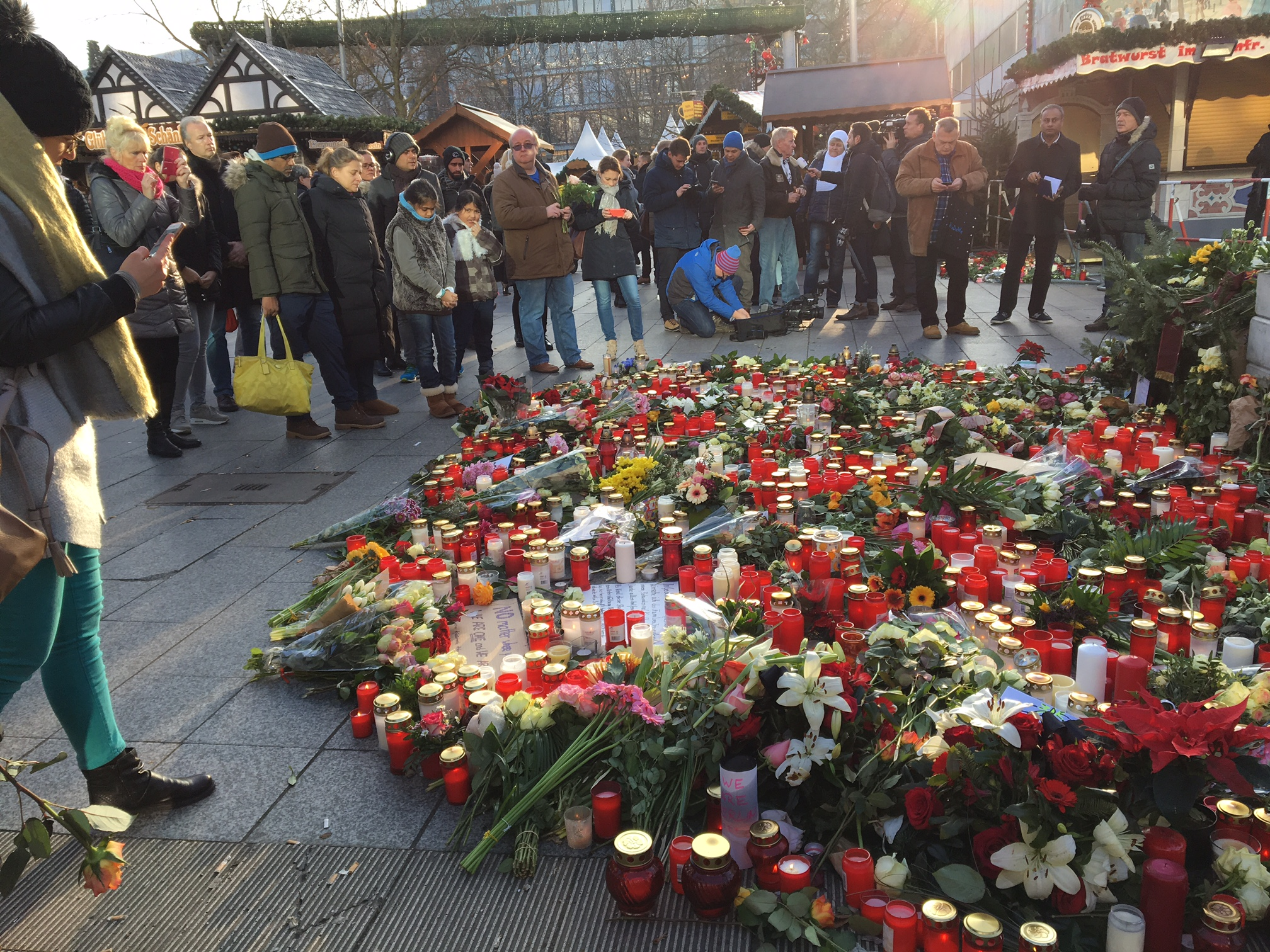 Visitors to the Christmas Market in Berlin stop at a shrine for the 12 who died in the  terrorist attack